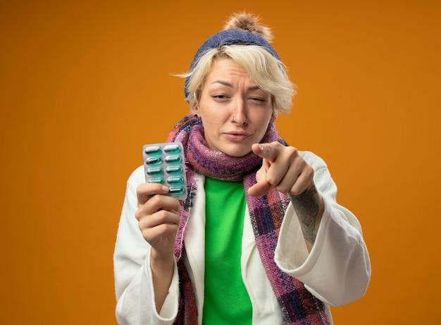 Больная нездоровая женщина с короткими волосами в теплом шарфе и шляпе, держащая блистер с таблетками, указывающая указательным пальцем в камеру, выглядит нездоровой, стоя на оранжевом фоне