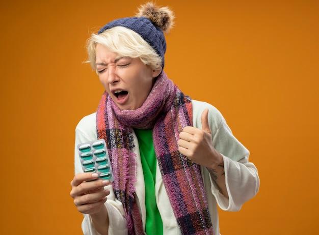 Больная нездоровая женщина с короткими волосами в теплом шарфе и шляпе, держащая блистер с кричащими таблетками, стоит над оранжевой стеной