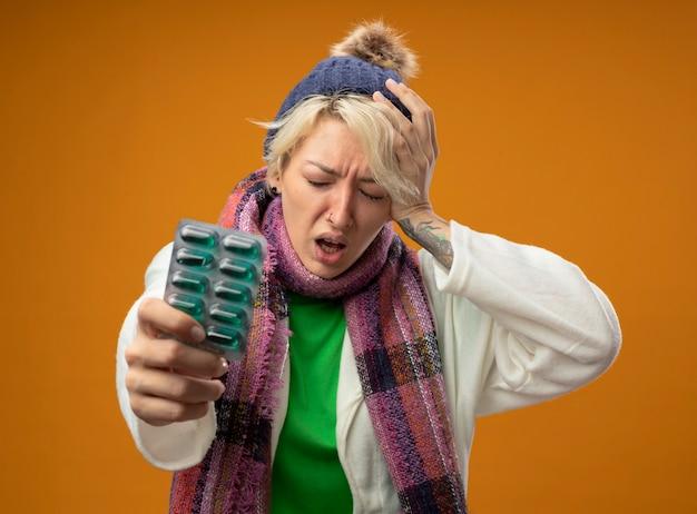Больная нездоровая женщина с короткими волосами в теплом шарфе и шляпе, держащая блистер с таблетками, касающимися ее головы, выглядит смущенной, стоя над оранжевой стеной