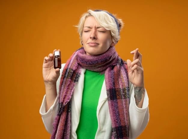 Больная нездоровая женщина с короткими волосами в теплом шарфе и шляпе держит бутылку с лекарством, загадывая желание с закрытыми глазами, скрещивая пальцы, стоя над оранжевой стеной
