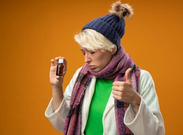 오렌지 배경 위에 서있는 슬픈 표정으로 엄지 손가락을 보여주는 약 병을 들고 따뜻한 스카프와 모자에 짧은 머리를 가진 아픈 건강에 해로운 여자