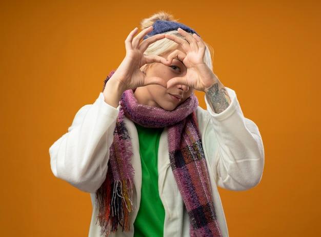 暖かいスカーフと帽子の短い髪の病気の不健康な女性は、オレンジ色の壁の上に立っていると気分が良くなる指を通して見ている指でヘラートのジェスチャーをしています