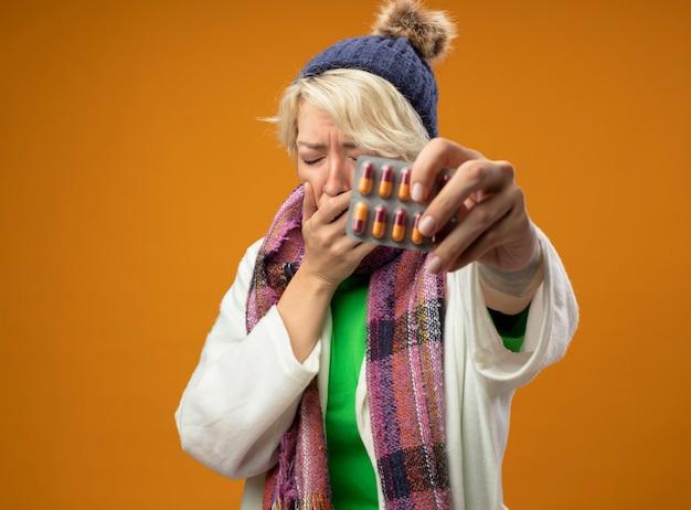 Больная нездоровая женщина с короткими волосами в теплом шарфе и шляпе показывает волдырь с таблетками, чувствуя тошноту, стоя на оранжевом фоне