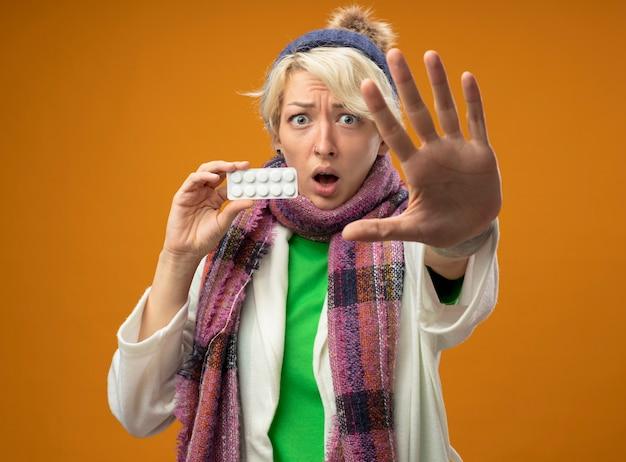 暖かいスカーフと帽子の短い髪の病気の不健康な女性は、オレンジ色の背景の上に立って心配し、怖がっている手で停止ジェスチャーをしている丸薬で水ぶくれを示しています