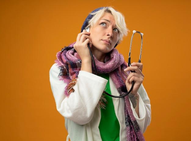 オレンジ色の背景の上に立って困惑して見上げる聴診器と暖かいスカーフと帽子の短い髪の病気の不健康な女性