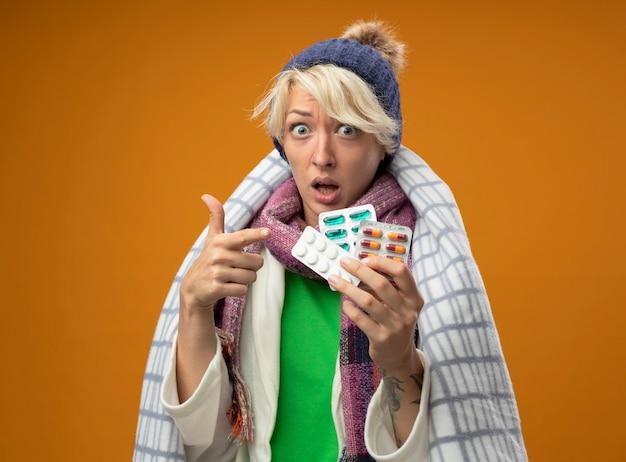 따뜻한 스카프와 모자에 짧은 머리를 가진 아픈 건강에 해로운 여자는 오렌지 벽 위에 서서 걱정하는 그들에게 손가락으로 약을 들고 담요에 싸여 있습니다.