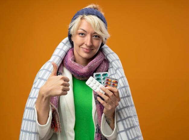 Больная нездоровая женщина с короткими волосами в теплом шарфе и шляпе, завернутой в одеяло, держит таблетки, улыбаясь, показывает палец вверх, чувствуя себя лучше, стоя над оранжевой стеной