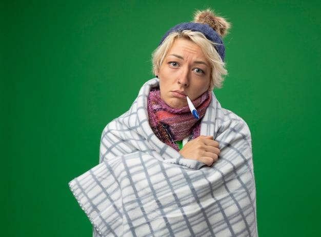 Больная нездоровая женщина с короткими волосами в теплом шарфе и шляпе, завернутая в одеяло, с термометром во рту, имеющая температуру, стоящую на зеленом фоне