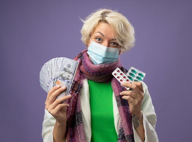 Больная нездоровая женщина с короткими волосами в теплом шарфе и защитной маске для лица держит деньги и блистер с таблетками, улыбаясь, стоя над фиолетовой стеной