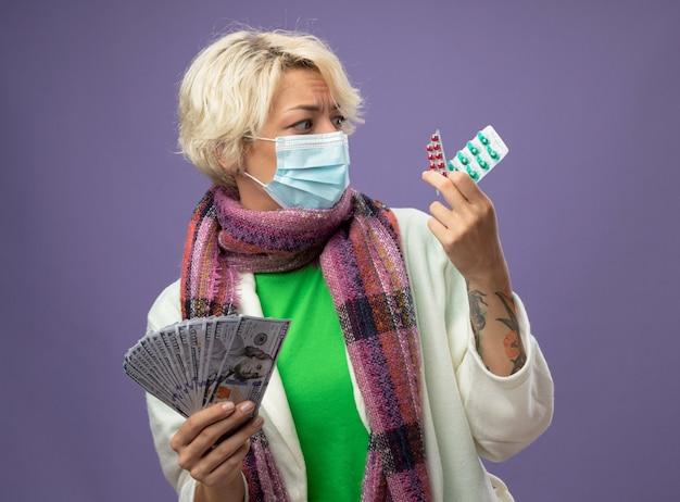 Больная нездоровая женщина с короткими волосами в теплом шарфе и защитной маске для лица держит деньги и таблетку, выглядит смущенной и обеспокоенной, сомневаясь, стоя на фиолетовом фоне