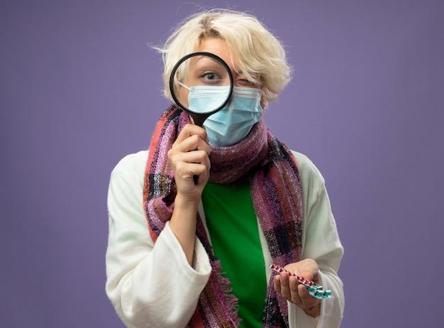 보라색 벽 위에 서있는 약을 들고 돋보기를 통해 따뜻한 스카프와 얼굴 보호 마스크에 짧은 머리를 가진 아픈 건강에 해로운 여자