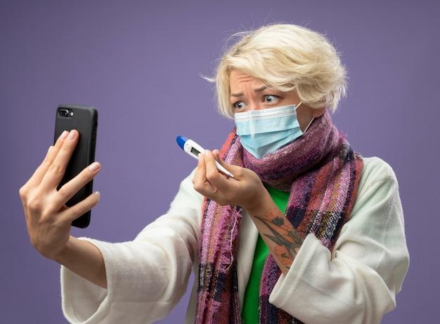 Donna malata malsana con i capelli corti in sciarpa calda e maschera protettiva per il viso tenendo il termometro con videochiamata utilizzando mobilestanding sul muro viola