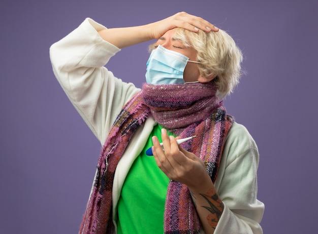 Malata malsana donna con i capelli corti in calda sciarpa andfacial maschera protettiva tenendo il termometro toccando la sua testa con gli occhi chiusi su sfondo viola
