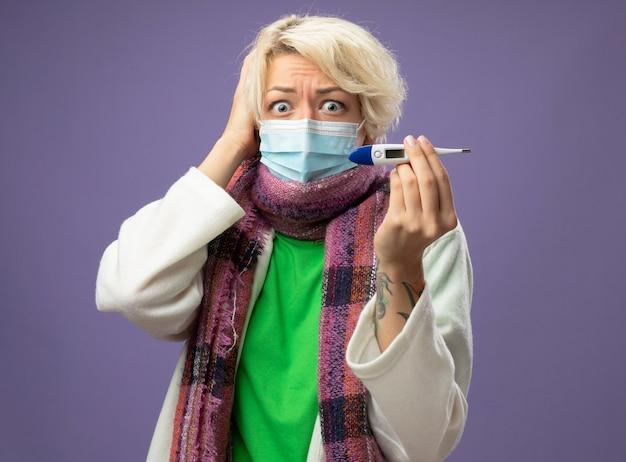Malata malsana donna con i capelli corti in calda sciarpa andfacial maschera protettiva che mostra il termometro guardando la fotocamera in preda al panico su sfondo viola