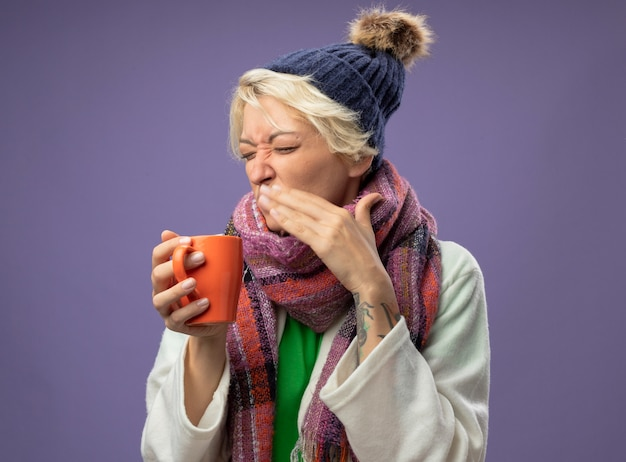 Sick unhealthy woman with short hair in warm scarf and hat feeling unwell holding cup of hot tea going to drink with disgusted expression standing over purple wall