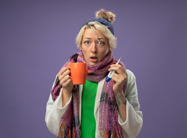 Sick unhealthy woman with short hair in warm scarf and hat feeling unwell holding cup of hot tea and thermometer looking at camera looking at camera worried standing over purple background