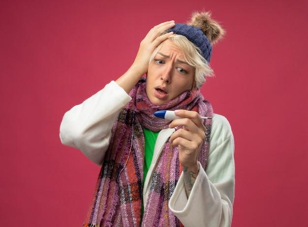 Donna malata malsana con i capelli corti in sciarpa calda e cappello sensazione di malessere guardando il termometro preoccupato e confuso in piedi sopra il muro rosa