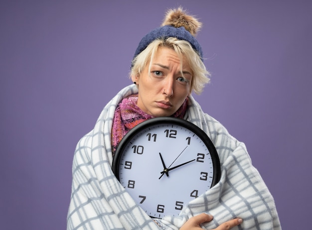 Sick unhealthy woman with short hair in warm scarf and hat feeling unwell wrapped in blanket holding wall clock looking at camera with sad expressionover purple background