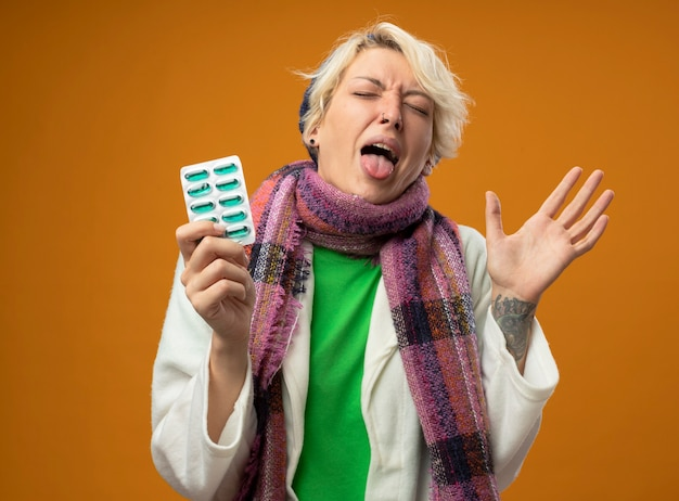 Sick unhealthy woman with short hair in warm scarf and hat holding blister with pills raising arm sticking out tongue with disgusted expression standing over orange background