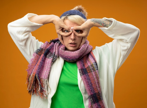 Sick unhealthy woman with short hair in warm scarf and hat making binocular gesture with fingers standing over orange wall
