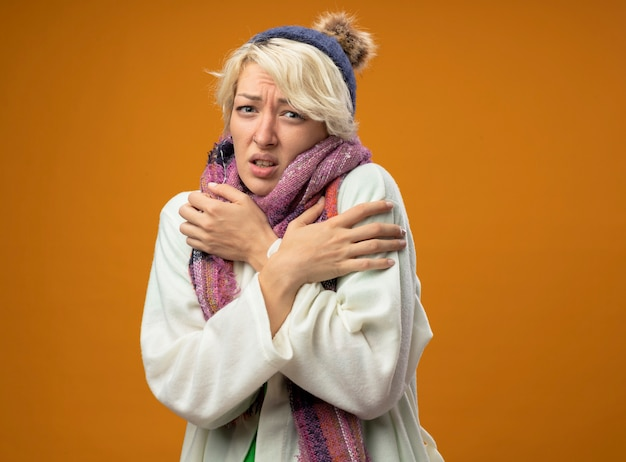 Donna malsana malata con capelli corti in sciarpa calda e cappello che soffrono di febbre sensazione di malessere in piedi sopra il muro arancione