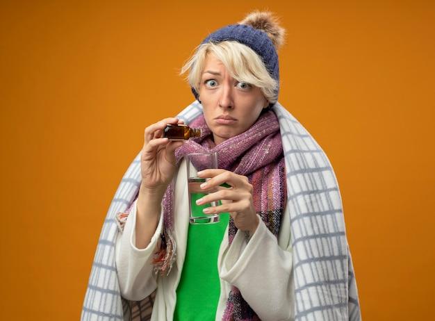 Donna malata malsana con capelli corti in sciarpa calda e cappello avvolto in una coperta gocciolante gocce di medicina in un bicchiere guardando la telecamera confusa in piedi su sfondo arancione