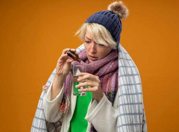 Donna malsana malata con capelli corti in sciarpa calda e cappello avvolto in una coperta gocciolante gocce di medicina in un bicchiere in piedi su sfondo arancione