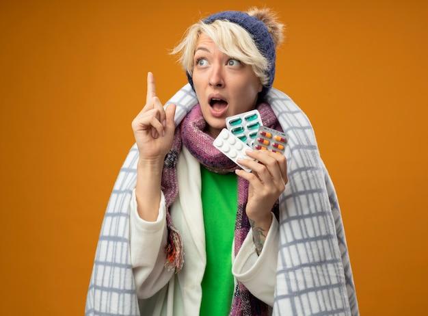 Malata malsana donna con i capelli corti in calda sciarpa e cappello avvolto in una coperta azienda pillole cercando che mostra il dito indice in piedi su sfondo arancione