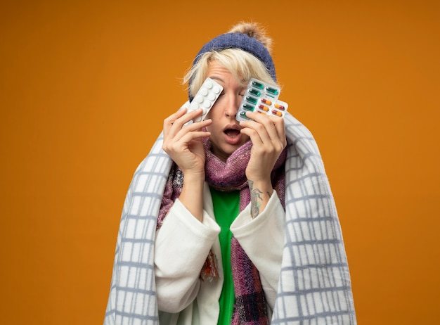 Sick unhealthy woman with short hair in warm scarf and hat wrapped in blanket holding plls covering eyes with them standing over orange background
