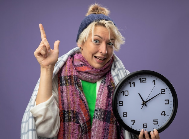 Donna malsana malata con capelli corti in sciarpa calda e cappello avvolto in una coperta che tiene l'orologio da parete che si sente meglio mostrando il dito indice che sorride sulla parete viola