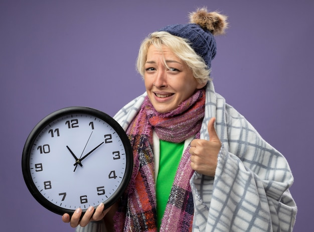 Sick unhealthy woman with short hair in warm scarf and hatwrapped in blanket holding wall clock looking at camera feeling better showing thumbs up smilingover purple background