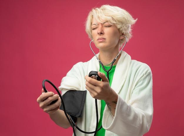 ピンクの背景の上に立っている彼女の血圧を測定する聴診器で短い髪の病気の不健康な女性