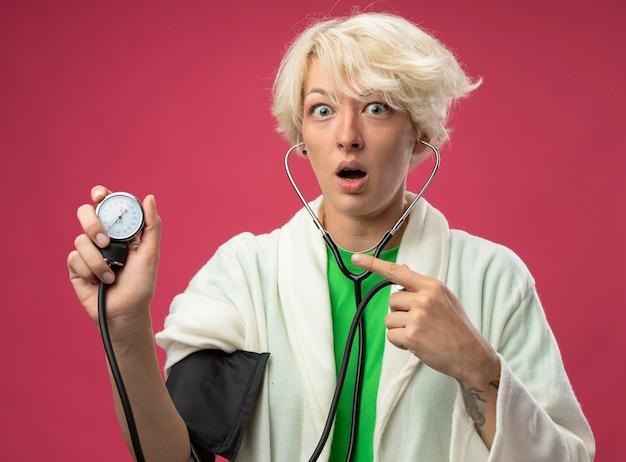 Больная нездоровая женщина с короткими волосами со стетоскопом, измеряющая ее кровяное давление, в панике стоит над розовой стеной