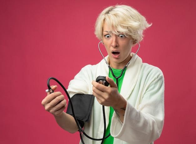 Больная нездоровая женщина с короткими волосами со стетоскопом, измеряющая ее кровяное давление, выглядит обеспокоенной, стоя на розовом фоне