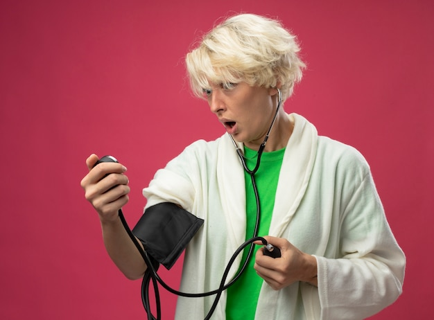 Donna malata malsana con i capelli corti con lo stetoscopio che misura la sua pressione sanguigna streesed e nervosa in piedi su sfondo rosa