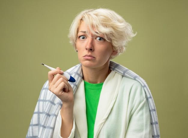 Donna malata malsana con i capelli corti avvolti in una coperta sensazione di malessere tenendo il termometro guardando la telecamera con espressione triste che soffre di influenza in piedi su sfondo chiaro