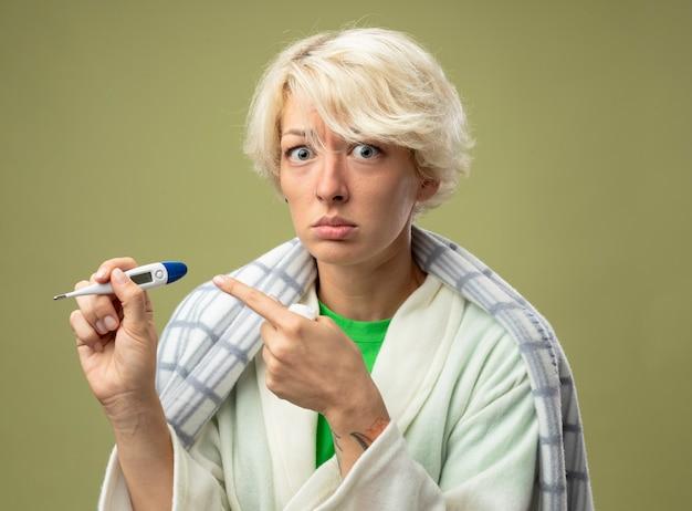 Malata malsana donna con i capelli corti avvolti in una coperta sensazione di malessere tenendo il termometro puntato con il dito indice su di esso con espressione triste che soffre di influenza