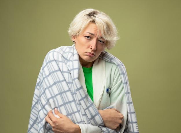 Malata malsana donna con i capelli corti avvolti in una coperta sensazione di malessere che soffre di febbre in piedi sopra la parete chiara