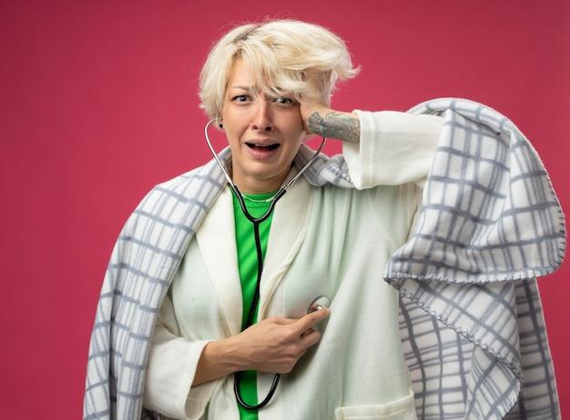 Donna malata malsana con i capelli corti avvolti in una coperta con lo stetoscopio intorno al collo ascoltando il suo battito cardiaco sensazione di malessere stressata e nervosa in piedi su sfondo rosa