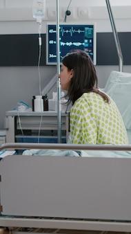クリップボードに医学的病気の治療を書いている病気の専門知識を調べている開業医がベッドに座っている病気の女性の大人
