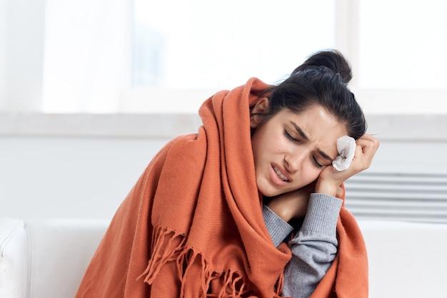Больная женщина дома прячется с одеялом, проблемы со здоровьем