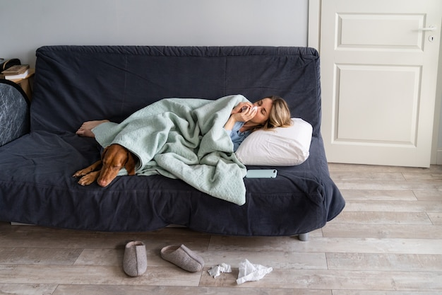 Больная женщина дома, лежа в постели со своей собакой визсла, страдает аллергией, симптомом гриппа, лихорадкой
