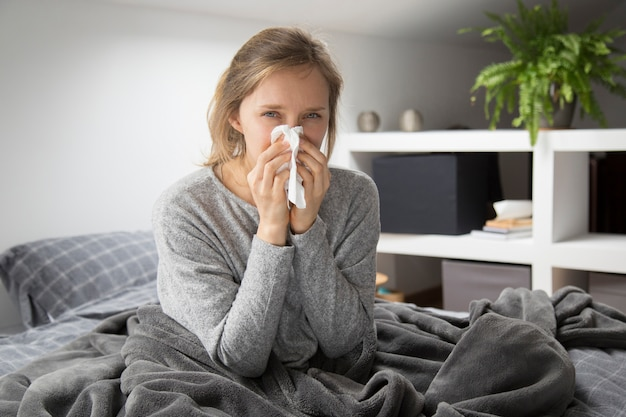 Sick woman in bed blowing nose with napkin, looking at camera