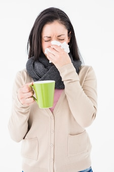 Sick woman blowing her nose while holding a green mug Premium Photo