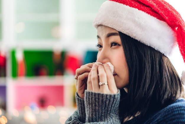 Sick woman blowing her nose with paper tissue and sneezing while having cold