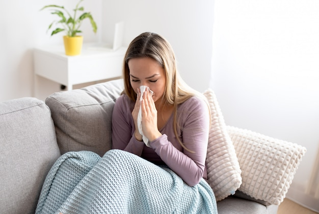 Sick woman blowing nose, sitting under the blanket