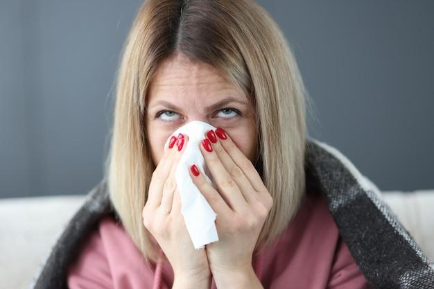 Больная женщина высморкалась в носовой платок с концепцией сезонной болезни