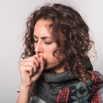 Sick woman coughing against gray background