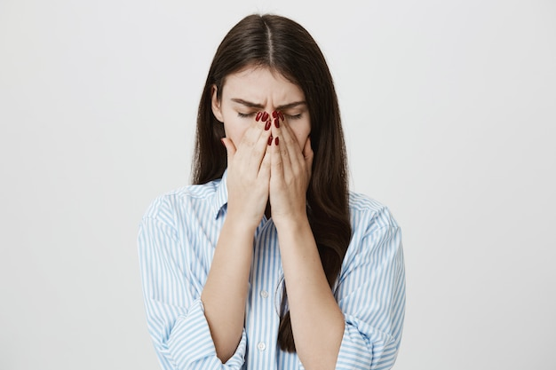 Sick woman coughing or sneezing in palms