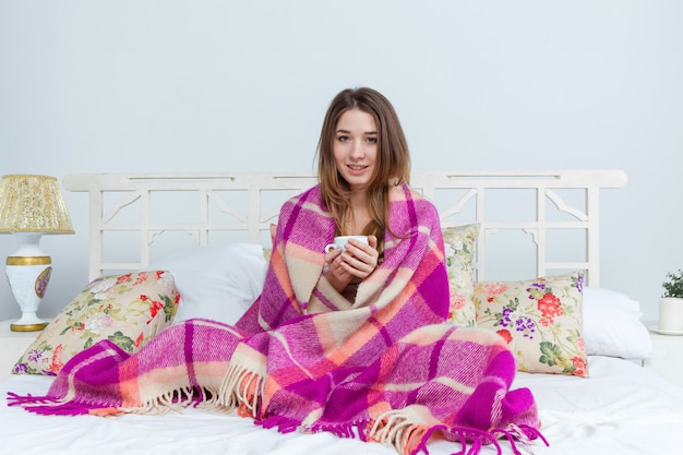 Sick woman covered with blanket holding cup of tea sitting on sofa couch at home